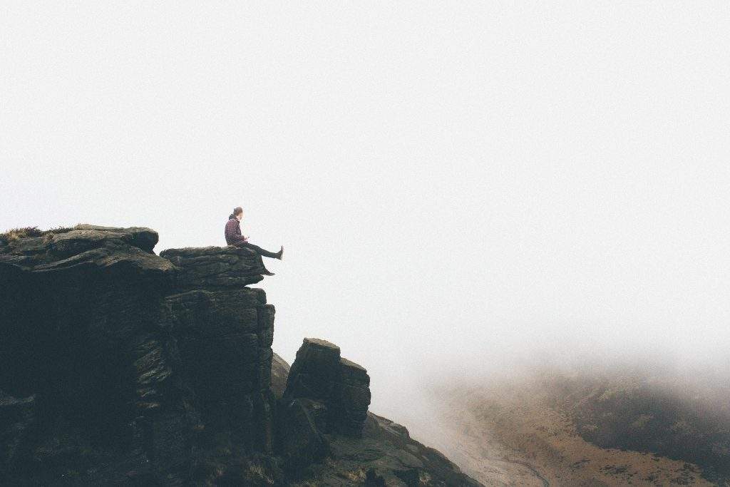 person sitting on the edge of a cliff